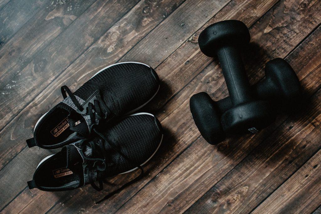 Ein Paar Schuhe neben Hanteln. Zum Trainieren lässt man die Schuhe besser an.